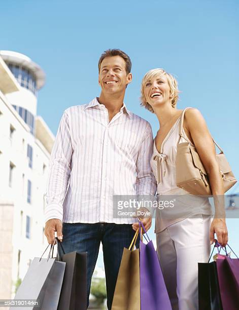 low angle view of a mid adult couple holding shopping bags