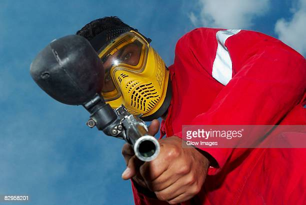 Low angle view of a mid adult man aiming with a paintball gun