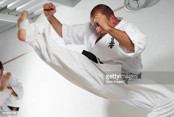 low angle view of a mid adult man practicing karate - obi sash stock pictures, royalty-free photos & images