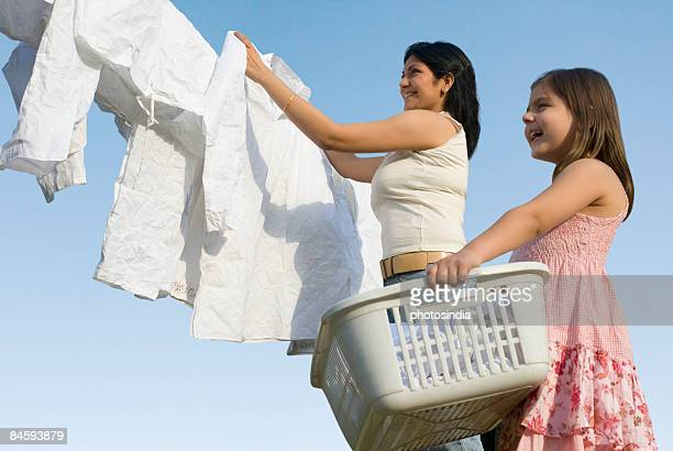 Low angle view of a mid adult woman and her daughter hanging clothes on a clothesline