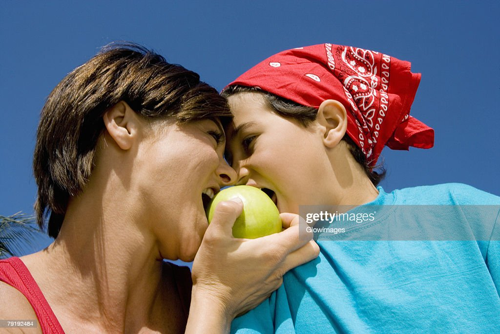Low angle view of a mid adult woman biting an apple with her son : Stock Photo