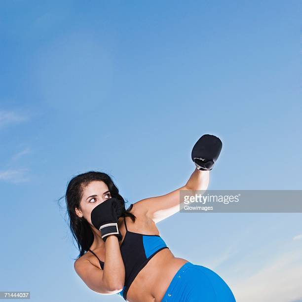 low angle view of a mid adult woman punching - belly punch stock pictures, royalty-free photos & images