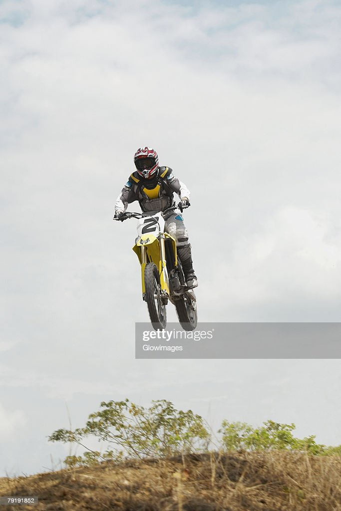 Low angle view of a motocross rider performing a jump on a motorcycle : Foto de stock