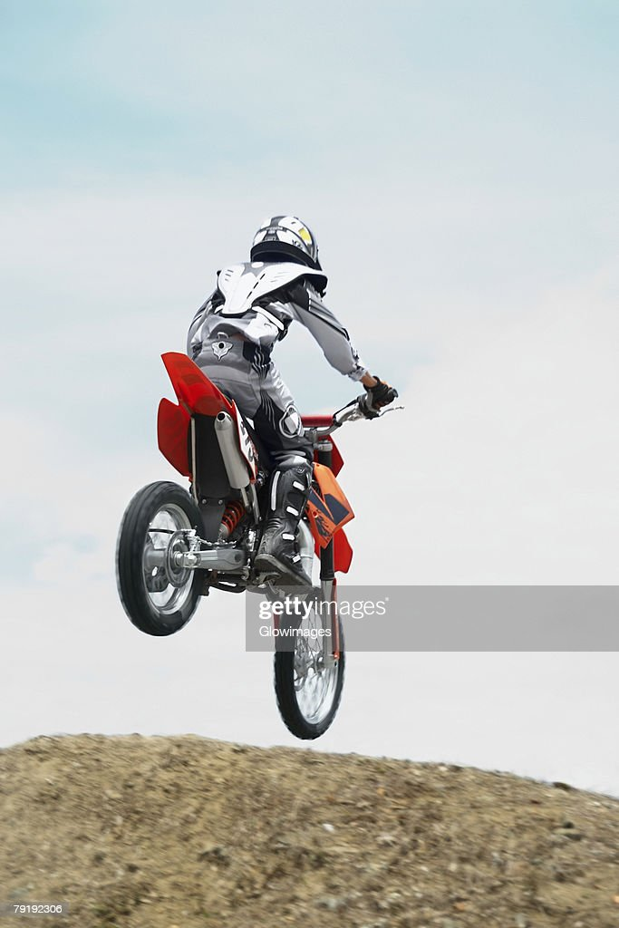 Low angle view of a motocross rider performing a jump on a motorcycle : Stock Photo