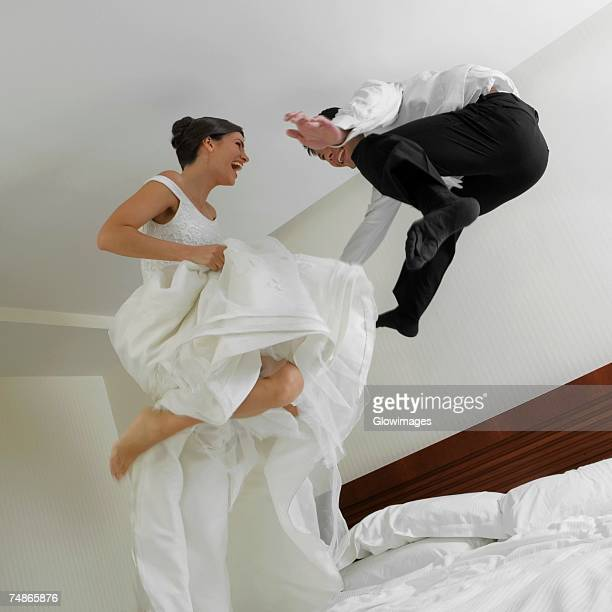 low angle view of a newlywed couple jumping on the bed - newlywed stock pictures, royalty-free photos & images