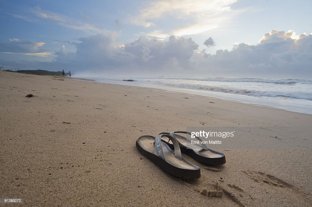 8ca24a3eb66097 Low angle view of a pair of sandals on the beach at sunrise with two people
