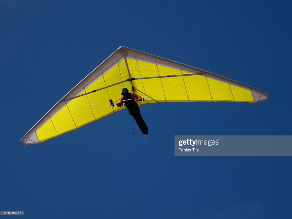 Low angle view of a person hang-gliding against clear blue sky : Stock Photo