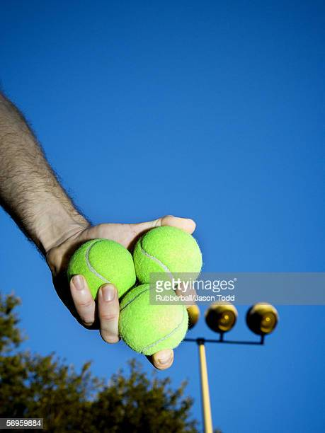 Low angle view of a person holding three tennis balls
