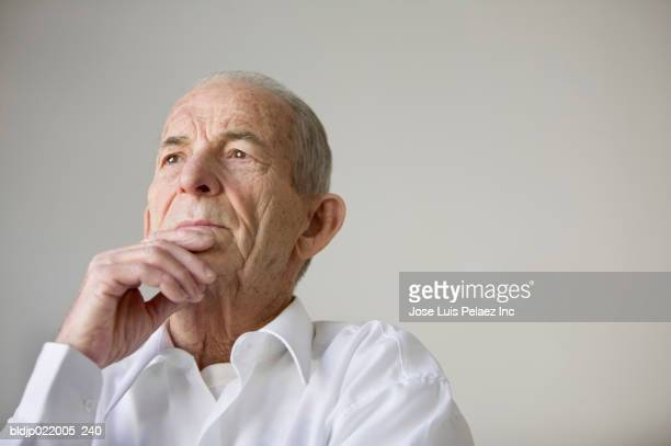 Low angle view of a senior man looking pensive