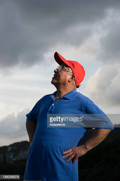 low angle view of a senior man standing with arms akimbo - arms akimbo stock photos and pictures
