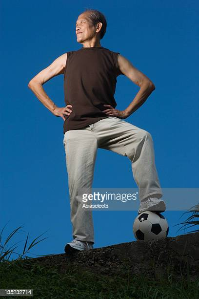low angle view of a senior man standing with his leg on a soccer ball - arms akimbo stock photos and pictures