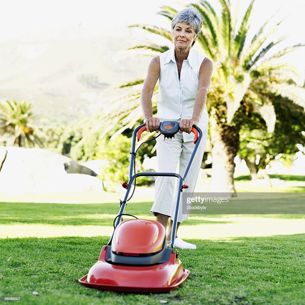 Woman Mowing The Lawn On Back Yard Of The House High-Res