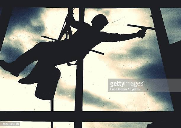 low angle view of a silhouette window cleaner - window cleaning stock photos and pictures