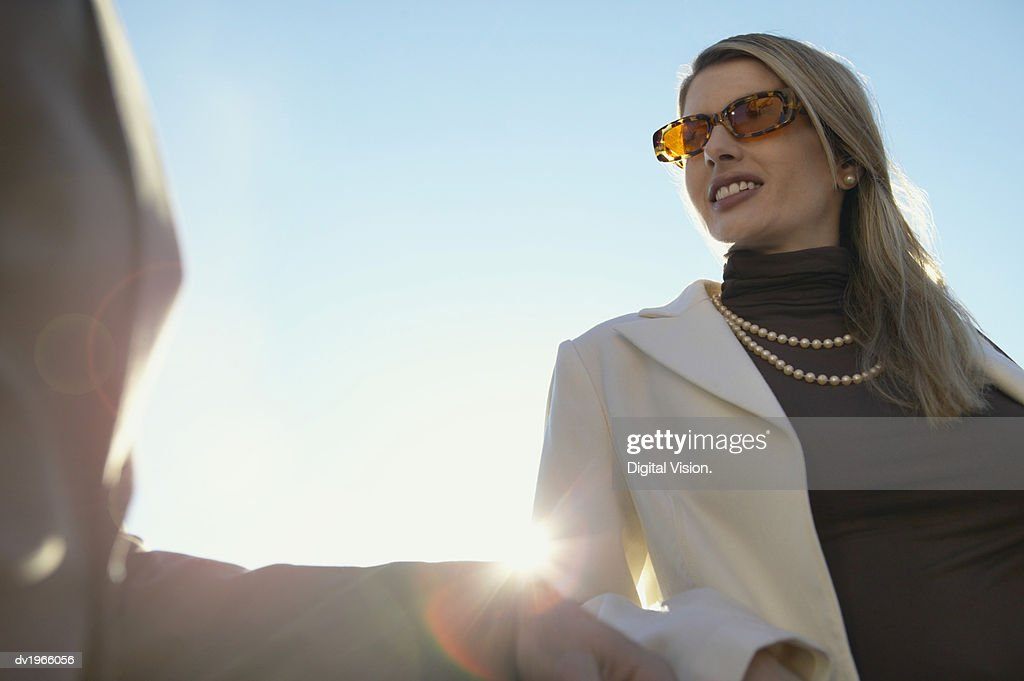 Low Angle View of a Smiling, Woman Looking Sideways : Stock Photo