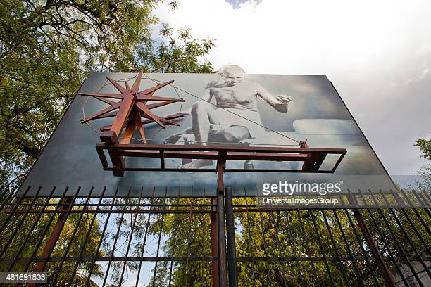 Low angle view of a spinning wheel with picture of Mahatma Gandhi on a hording Sabarmati Ashram Ahmedabad Gujarat India