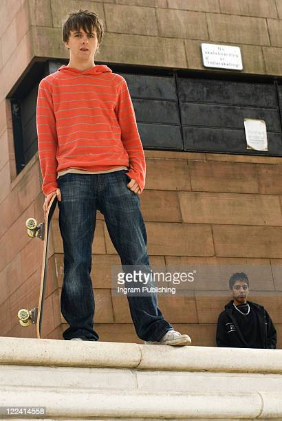 low angle view of a teenage boy holding a skateboard - low angle view photos et images de collection