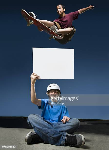 Low angle view of a teenage boy jumping with a skateboard over another teenage boy holding a blank sign