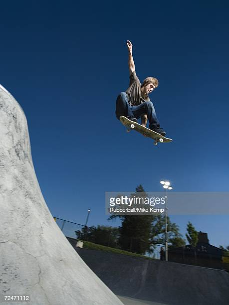 Low angle view of a teenage boy jumping with a skateboard
