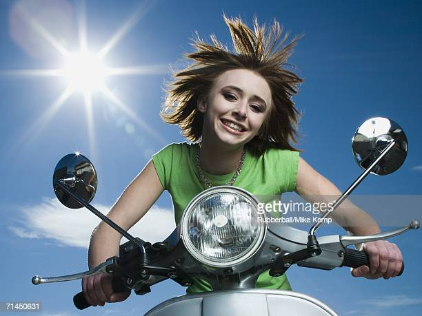 Low angle view of a teenage girl riding a scooter