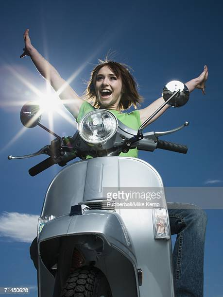 Low angle view of a teenage girl riding a scooter with her arms raised