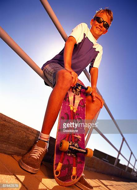 low angle view of a teenager sitting on a rail holding a skateboard