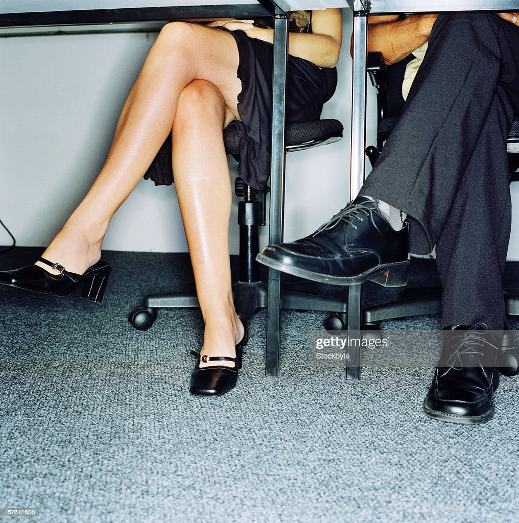 Low angle view of a the lower torso of a young man and a woman sitting on chairs : Stock Photo