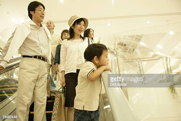 Low angle view of a three generation family on an escalator in a shopping mall
