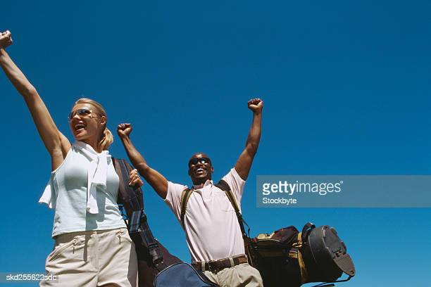 Low angle view of a two golfers with their arms raised in triumph