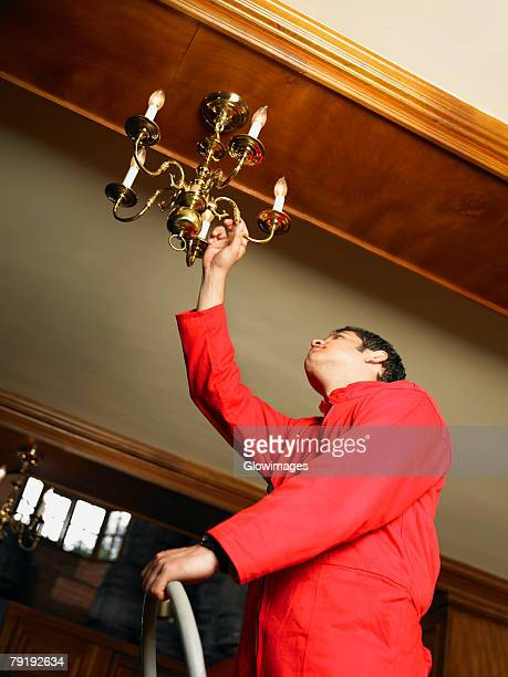 Low angle view of a waiter adjusting a chandelier