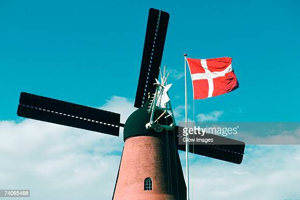 Low angle view of a windmill and the Danish flag, Funen County, Denmark