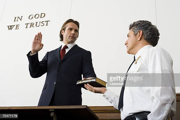Low angle view of a witness swearing over the Bible