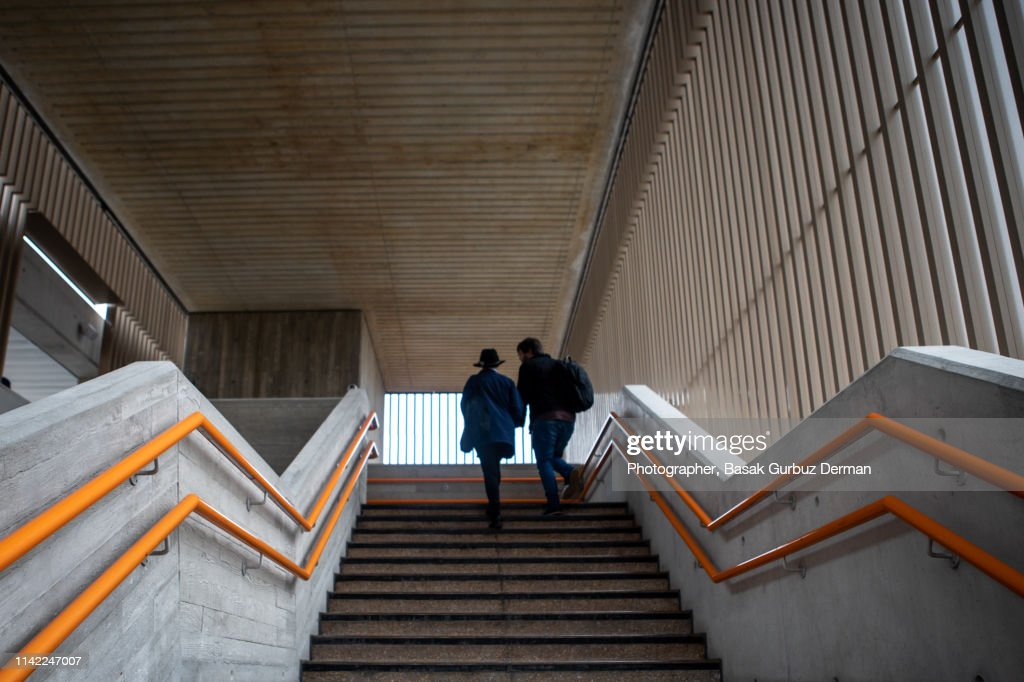 Low angle view of a woman and a man moving up the steps : Stock Photo