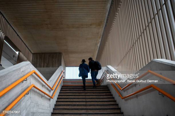 Low angle view of a woman and a man moving up the steps