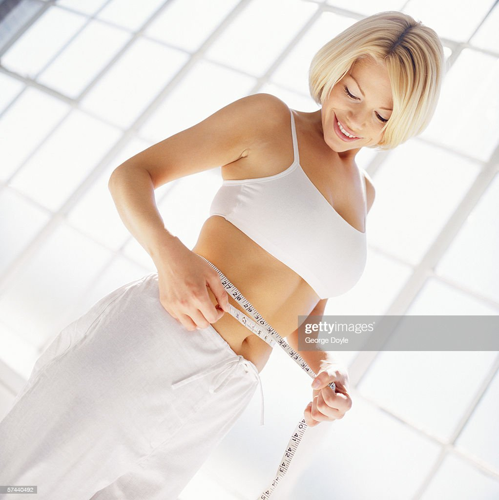 low angle view of a woman measuring her waist with an inch tape : Stock Photo
