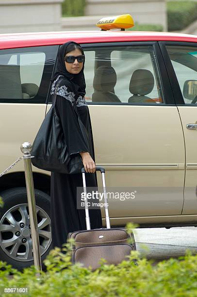 Low angle view of a woman standing at taxi with luggage, Dubai, UAE