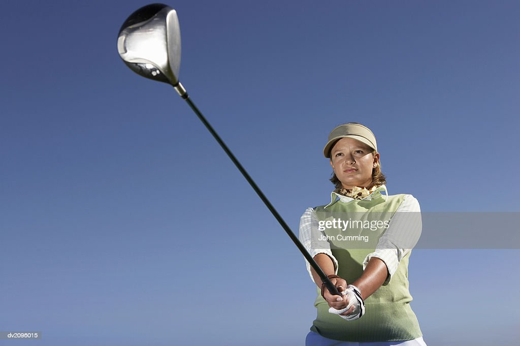 Low Angle View of a Woman Swinging a Golf Club : Stock Photo