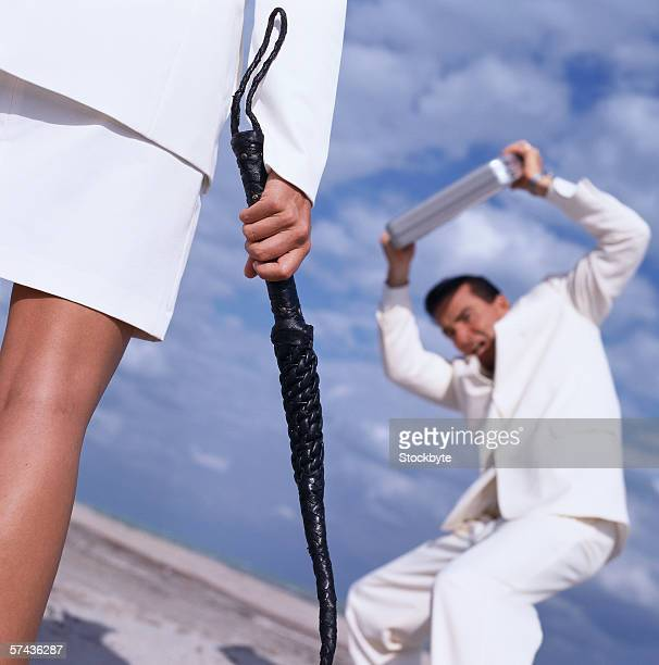 low angle view of a woman with a whip and a young man protecting himself with a briefcase - women whipping men stock photos and pictures