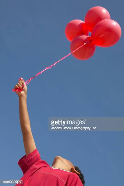 Low angle view of a young boy holding a bunch of balloons