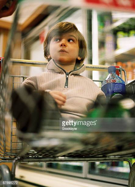 Low angle view of a young boy (4-6) sitting in a shopping cart