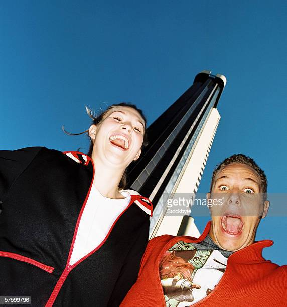 Low angle view of a young couple making faces