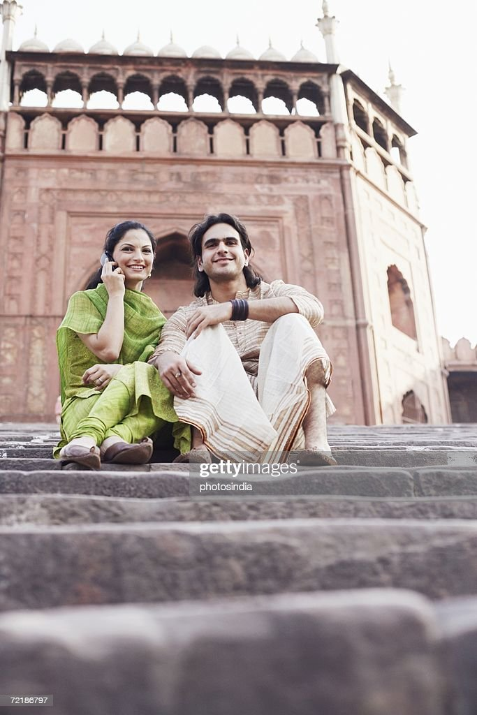 Low angle view of a young couple sitting on the steps in front of a building, Jama Masjid, Delhi, India : Stock Photo