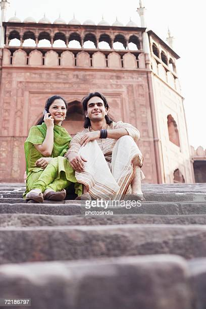 Low angle view of a young couple sitting on the steps in front of a building, Jama Masjid, Delhi, India