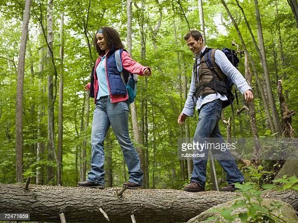 Low angle view of a young couple walking on a fallen tree
