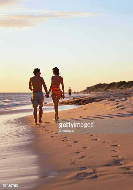 low angle view of a young couple walking on the beach