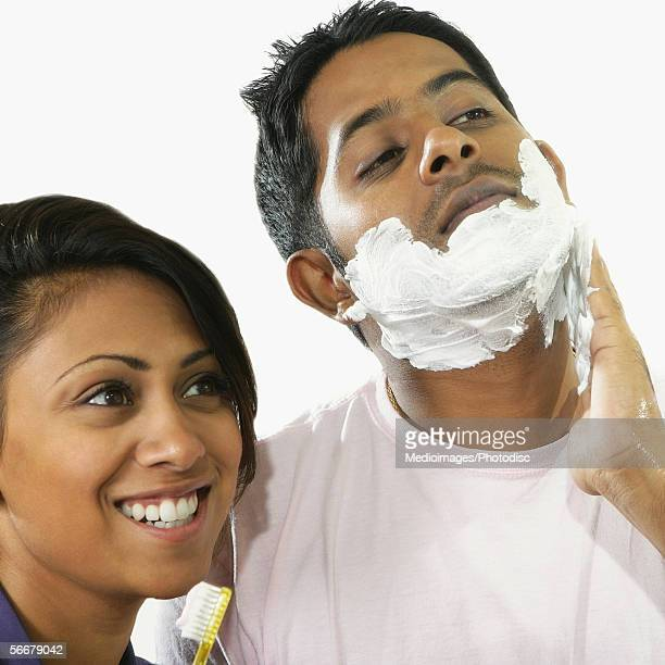 Low angle view of a young man applying shaving cream on his face and a young woman holding a toothbrush beside him