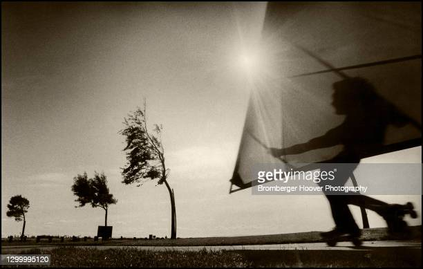 Low angle view of a young man as he wind surfs along a path at the San Leandro Marina, San Leandro, California, 1983.