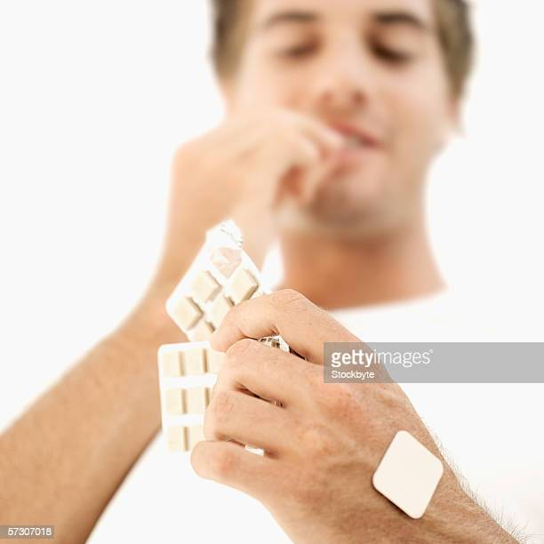 Low angle view of a young man eating nicotine gum from a strip