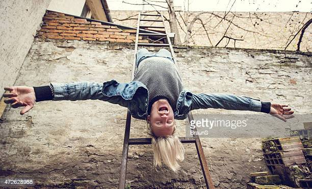Low angle view of a young man hanging from ladders.