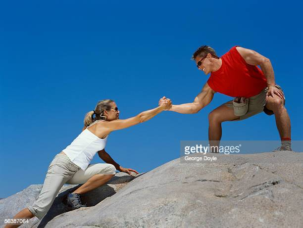 low angle view of a young man helping a young woman climb a rock