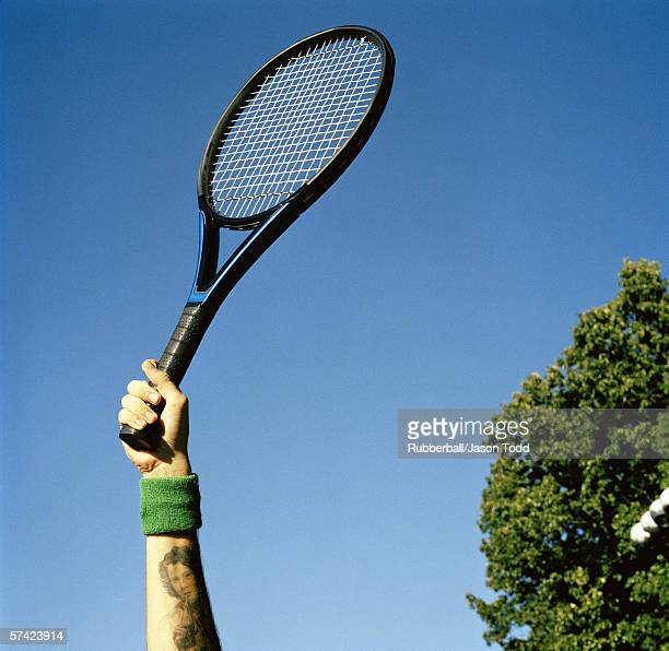 Low angle view of a young man holding a tennis racket